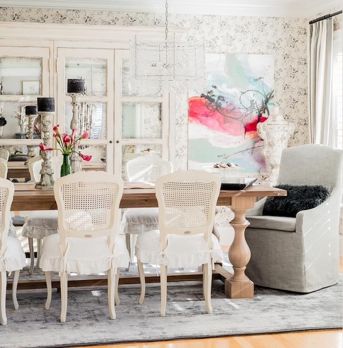 exemple de table salle à manger en bois avec des chaises vintage, fauteuil gris, tapis gris sur parquet bois clair, vaisselier blanc patiné