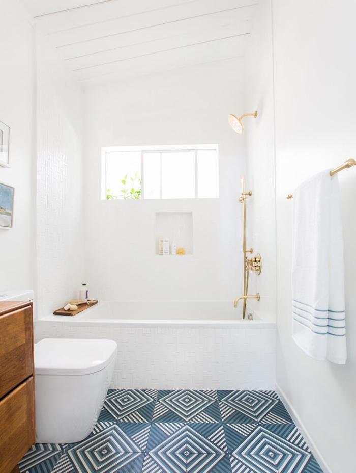 idée baignoire douche pour petit espace, déco de salle de bain blanche avec sol en carrelage graphique et finitions dorées