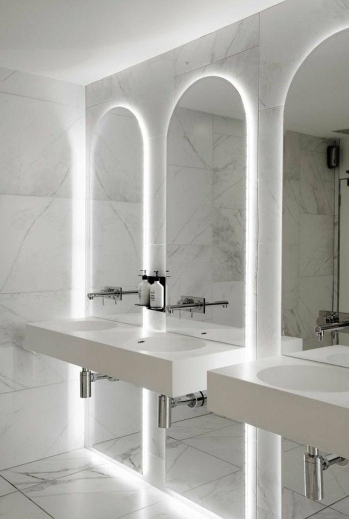 petite salle de bain moderne, déco salle de bain zen, murs recouverts de marbre blanc aux nervures noires, trois grandes arques illuminées par une lumière blanche discrète