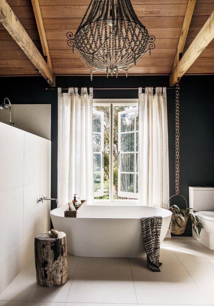 baignoire à poser blanche, carrelage gris clair, murs couleur noire, rideaux blancs, lustre baroque élégante, table de service en rondin de bois