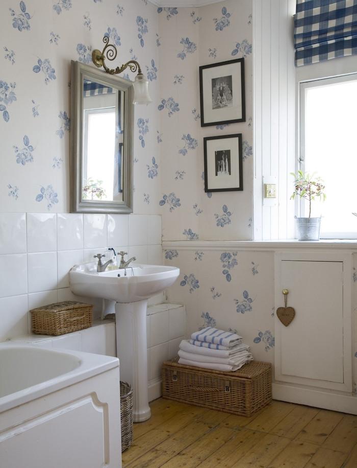 salle de bain habillée de papier peint, sol en parquet bois clair, lavabo console blanc, miroir vintage, baignoire à poser blanche