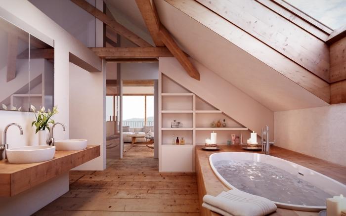modèle de salle de bain mansardée aménagée en style moderne avec meubles de bois et baignoire avec déco en fausse poutre