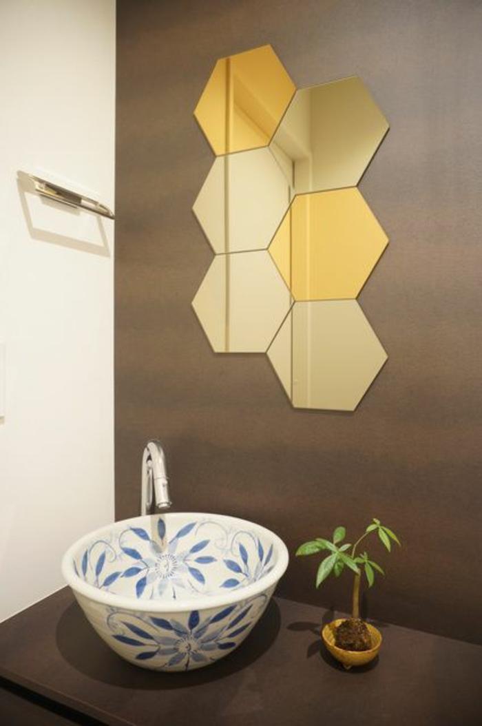petite salle de bain mdoerne, déco salle de bain zen, idee salle de bain, miroir en forme de six ruches aux lueurs dorées, lavabo rond aux motifs fleuris en bleu et blanc