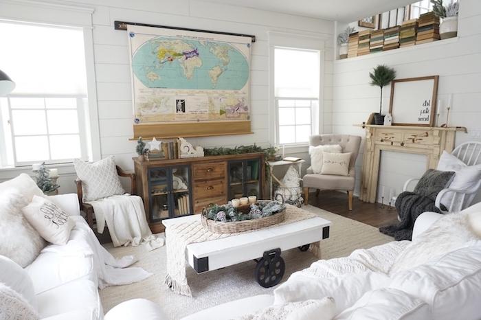deco mappemonde carte, fausse cheminée décorative, table basse bois blanche à roulettes, canapés blancs, meuble bas bois et metal rangement