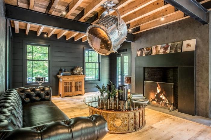 design intérieur moderne dans un salon gris anthracite avec cheminée noire et plafond en poutres de bois exposées