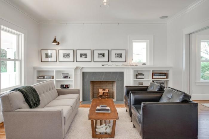 salon en gris et blanc, cadres peintures, sofas épurés, table longue en bois, tapis couleur crème, fausse cheminée