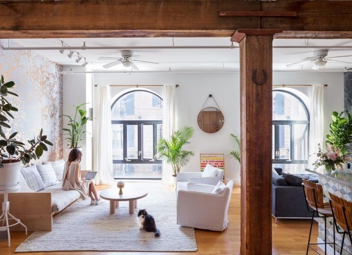 ambiance relaxante dans un studio aménagé en style scandinave et bohème chic avec plantes vertes et colonnes poutres décoratives en bois brut