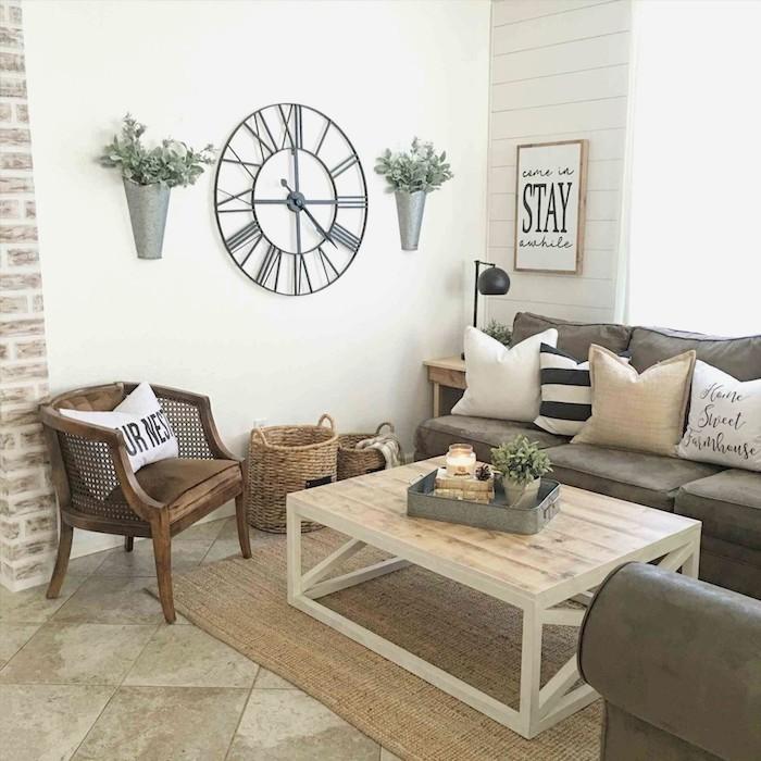 decoration campagne maison salon aux murs blancs, horloge vintage, canapé et fauteuil gris foncé, table basse bois et metal, sol carreaux de ciment, deco cadre ferme