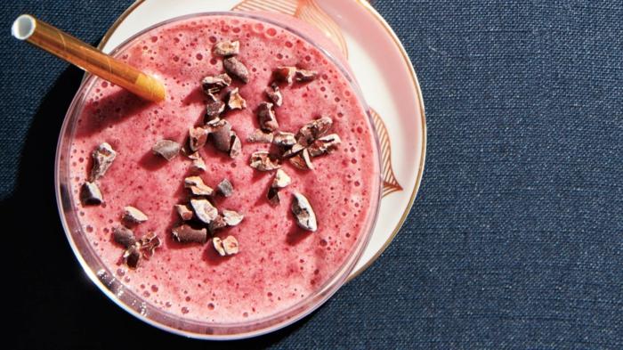 verre de milkshake fraise, boisson refroidie décorée de morceaux de noix, recette de milkshake