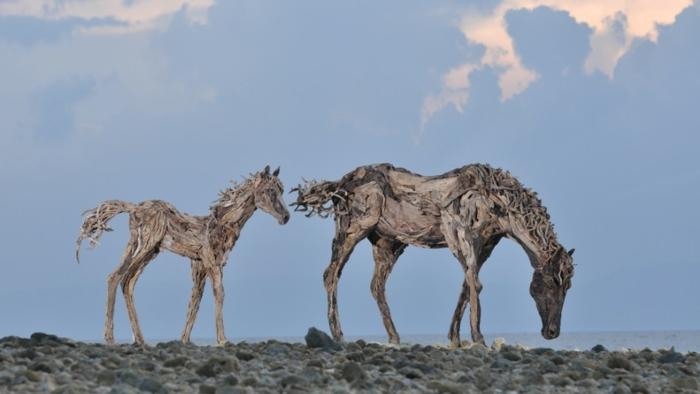 deux scultpures au bord de la mer, chevaux en bois flotté, figures super réalistes