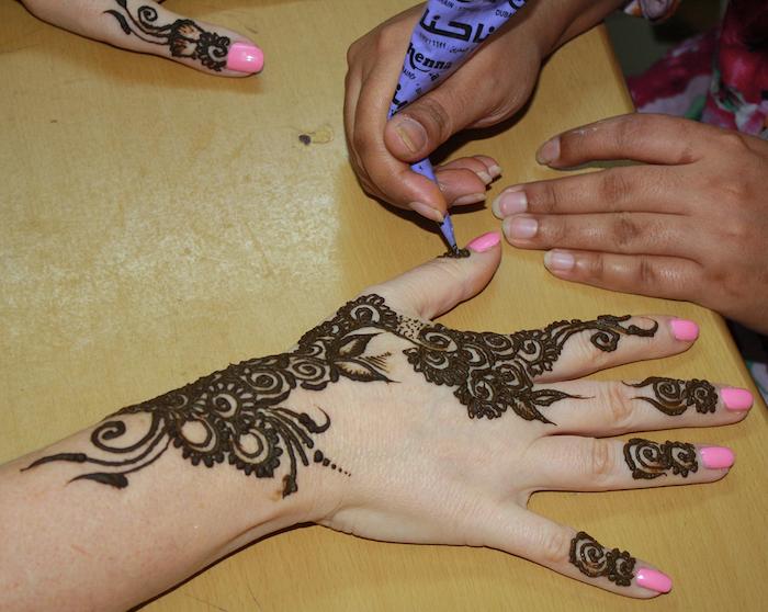 photo séance de tatouage au henné sur la main de femme avec ongles roses