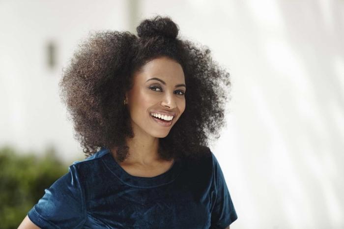 cheveux frisés femme, coiffure aux cheveux blow out avec un demi pin-up sur le haut de la tête, idée coiffure avec chignon haut sur cheveux lâchez crépus