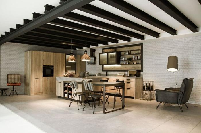 poutres noires au plafond, sol gris, ilot de cuisine avec rallonge table à manger, briques blanches