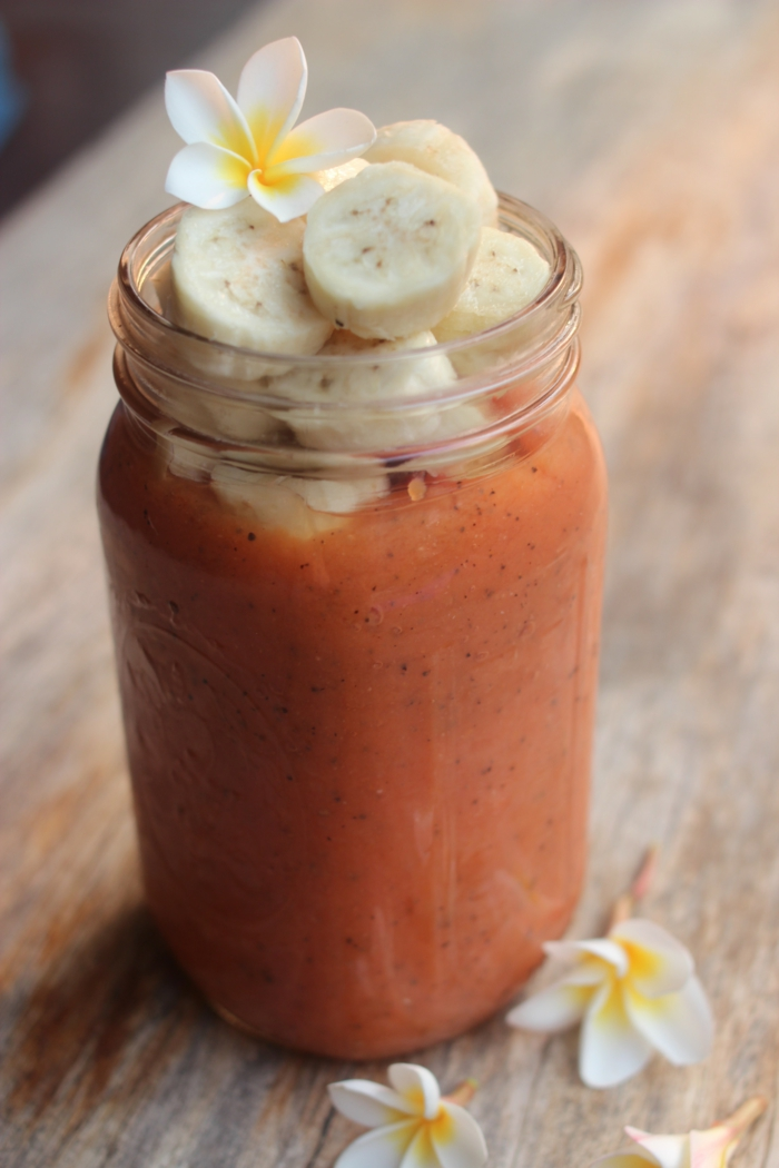 smoothie maison banane et papaye garni de tranches de fruits et d'une pétale