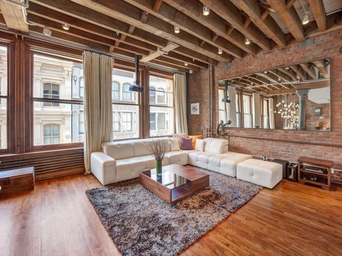 déco de salon spacieux de style industriel avec parquet bois et plafond à poutres exposées, modèle de canapé blanc en cuir