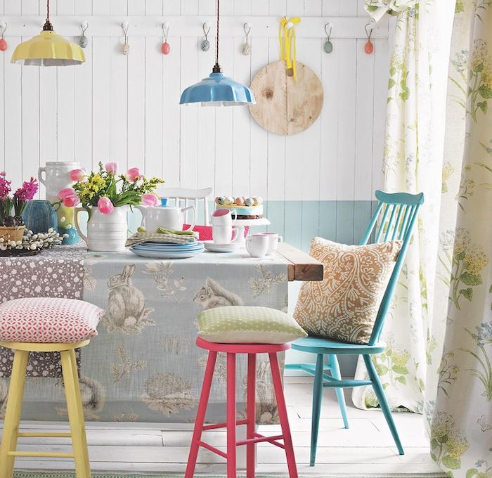 salle à manger style shabby avec chaises et tabourets dépareillées, table bois brut avec nappe à lapins, lambris blanc et bleu, vaisselle en blanc et pastel, suspensions originales