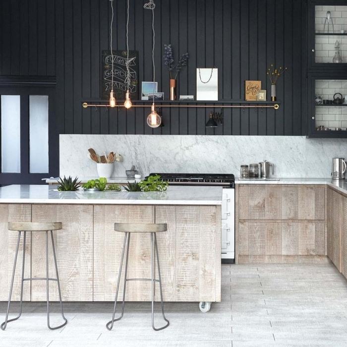 cuisine scandinave aux accents rustiques avec son revêtement mural partiel en lambris peint noir et ses armoires en bois rustique, cuisine avec ilot à roulettes avec des pots intégrés dans le comptoir pour des herbes aromatiques