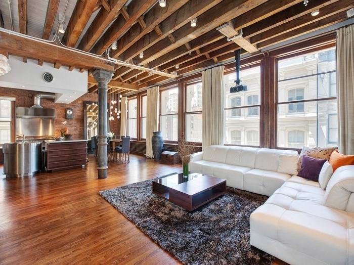 exemple de studio moderne aménagé dans style loft industriel et rustique avec cuisine équipée métal et plafond en poutres exposées