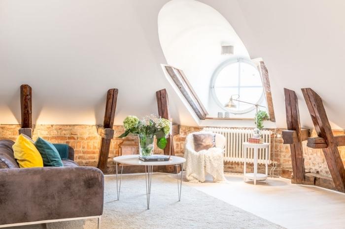 design intérieur moderne et cozy dans un salon sous pente avec murs blancs à déco briques rouges et poutres de bois apparentes