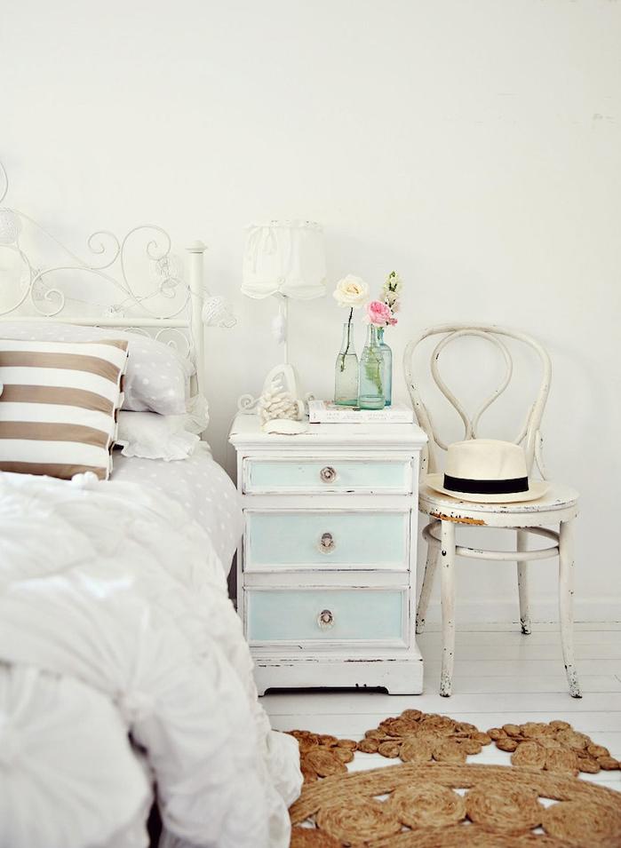 table de nuit patinée sous forme de meuble avec tiroirs, tapis rond original, linge de lit blanc sur un lit metallique blanc, deco chevet en soliflores, chaise vintage usée