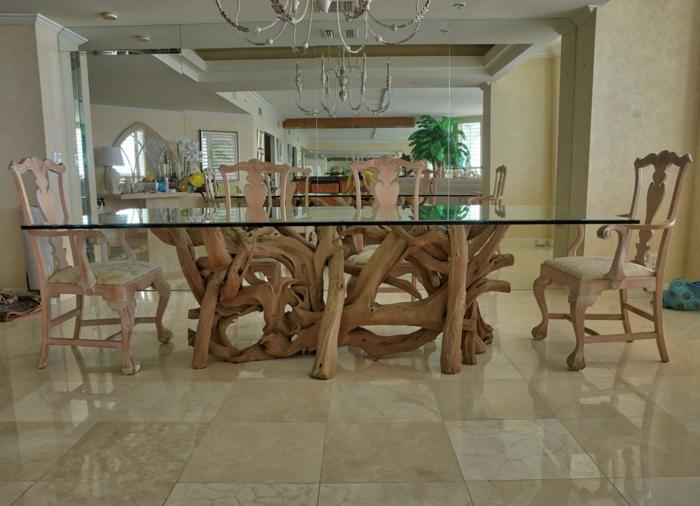 table de repas de bois flotté et verre, chaises en bois clair, sol en dalles beiges, chandelier