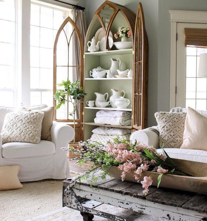 vaisselier en bois avec de la vaisselle blanche à l interieur, table bois brut à roulettes, tapis beige clair, canapé blanc, coussins décoratifs vintage