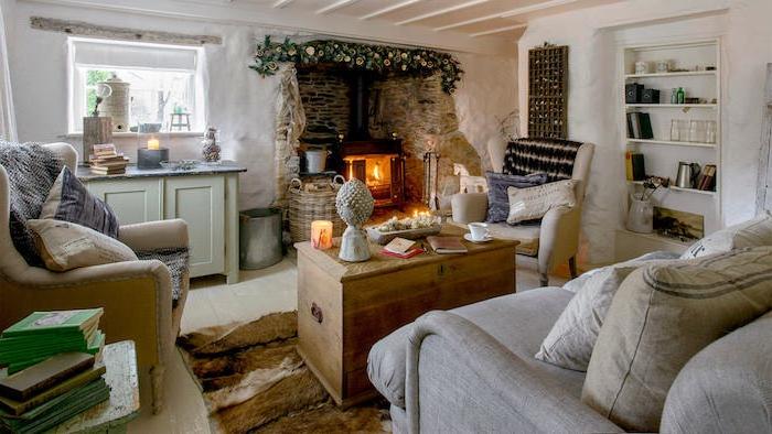 table basse en coffre de bois, canapé gris clair, fauteuil beige, tapis peau animal, cheminée rustique, niche murale, meubles bas rangement vintage