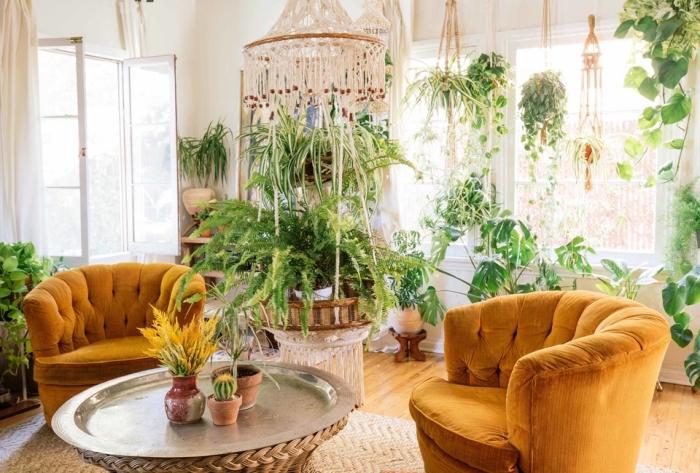 salon aménagée en style jungle bohème avec plantes vertes et meubles en bois et ratan, exemple suspensions pour plantes en macramé