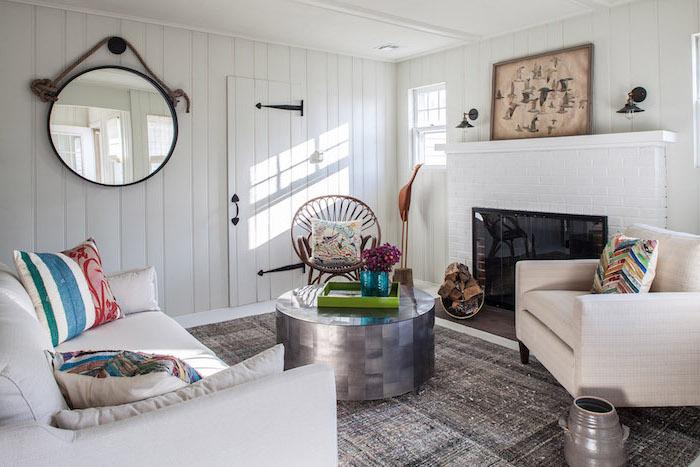 idée de deco campagne chic pour le salon cheminée moderne, miroir rond, canapé et fauteuil blancs, tapis gris, table basse ronde grise