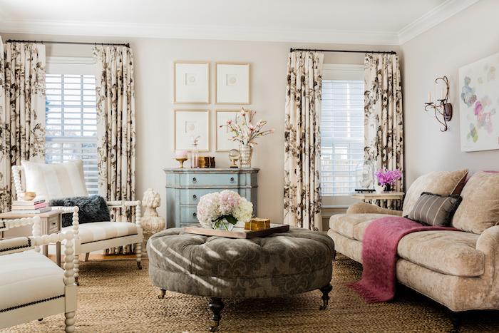 exemple de decoration campagne salon avec tapis beige, canapé marron clair, table basse ronde grise, chaises blanches, rideaux fleuris, commode ancienne bleue