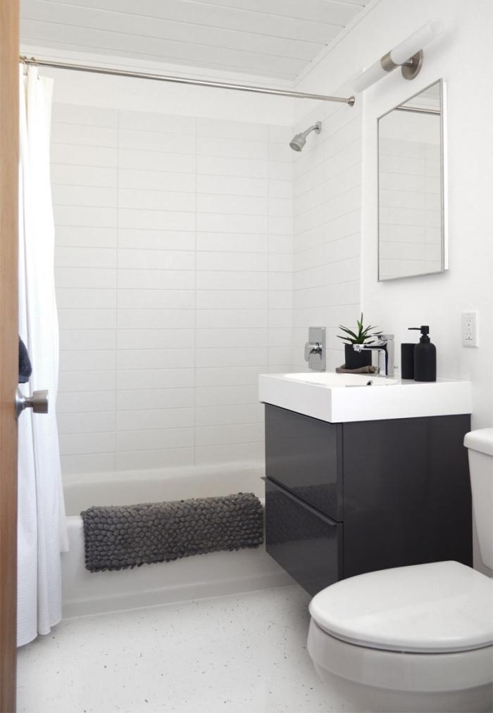 modèle de déco en blanc et noir dans une petite salle de bain avec baignoire douche, modèle meuble sous vasque blanc et noir laqué