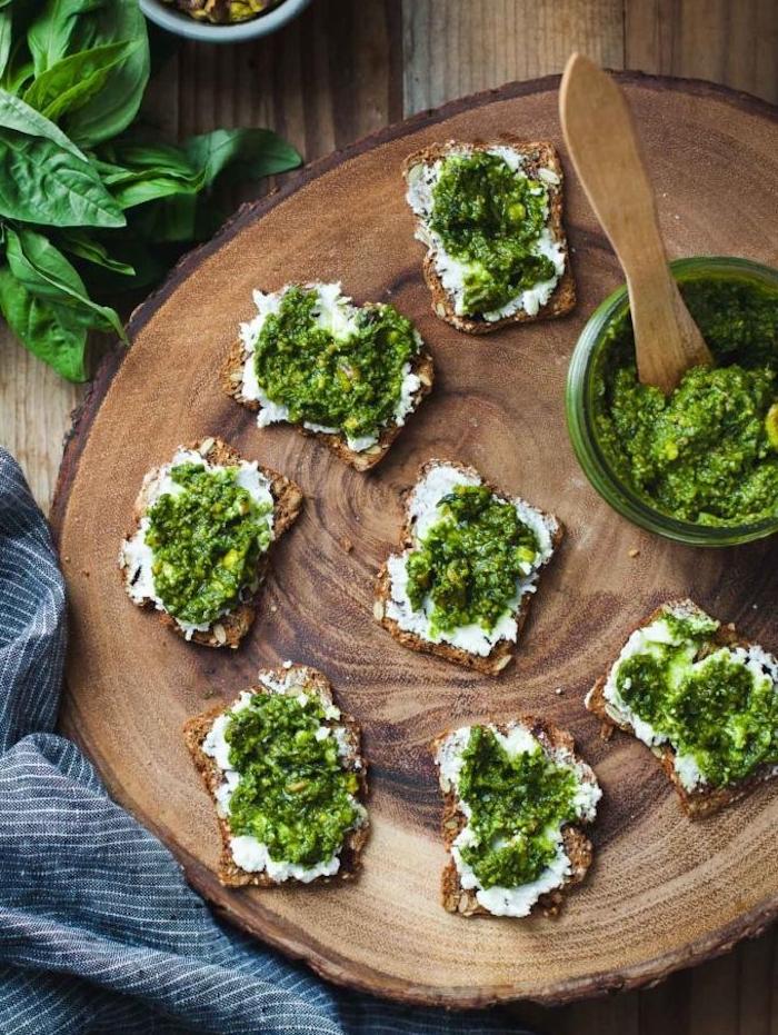 tartines de pain complet avec du fromage à la crème et pesto servis sur un rondin de bois rustique, idée amuse bouche apero froid