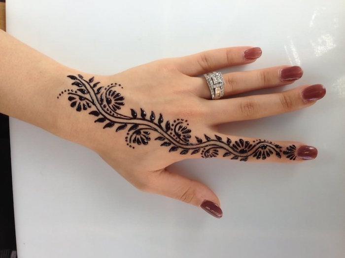 petit dessin eu henné noir sur la main partant du poignet au doigt