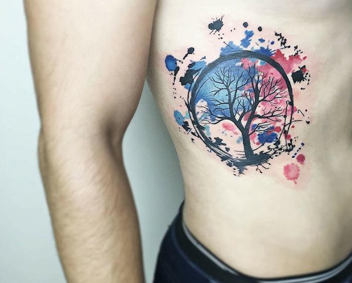 tattoo arbre de vie entouré en noir sur fond de taches en aquarelle bleu et rose sur cotes homme