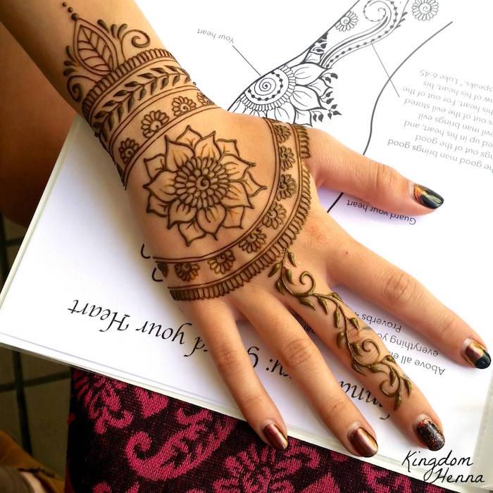 dessin de fleur lotus sur la main et bracelet au henné sur le poignet et doigt