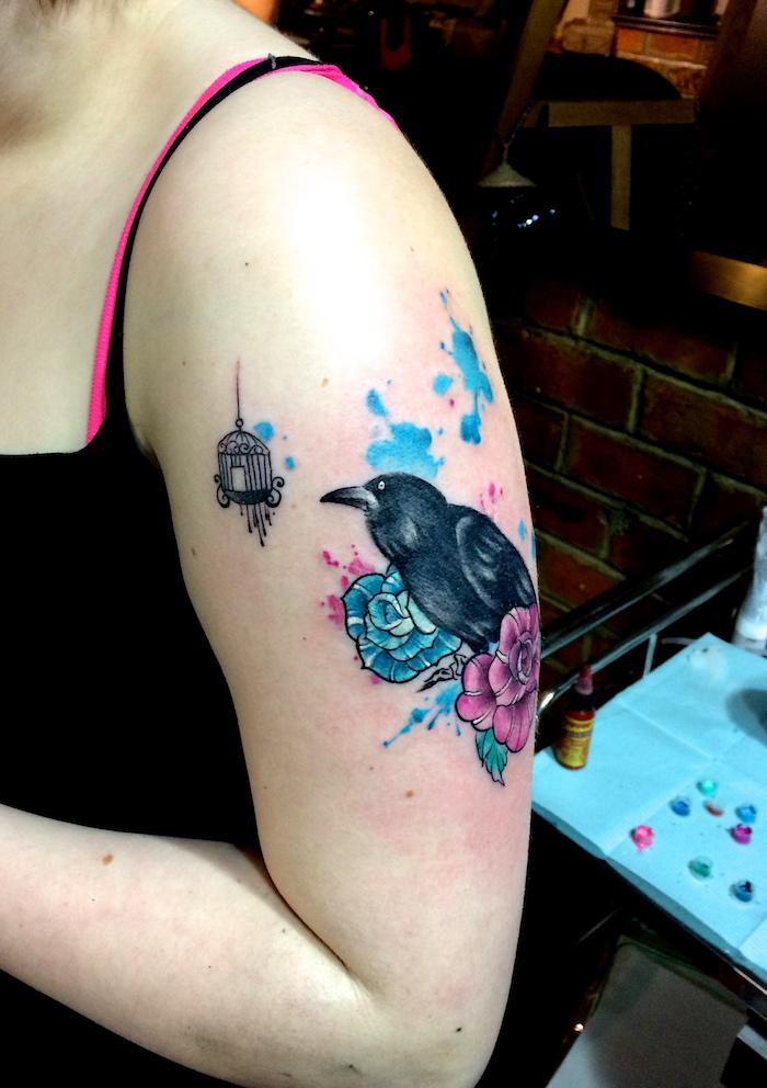 tattoo bras femme corbeau noir et fleurs turquoise et rose et taches aquarelle