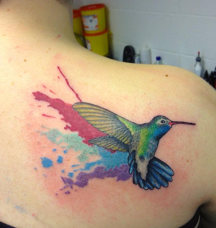 tatouage de colibri volant en couleurs aquarelle sur l'omoplate et dos femme