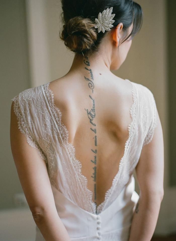 une robe de mariée dos nu en dentelle qui met en valeur le tatouage phrase sur la colonne vertébrale