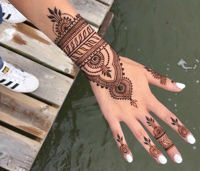dessin henné main sur doigts et poignet style bracelet en dentelle avec ongles blancs et adidas superstar