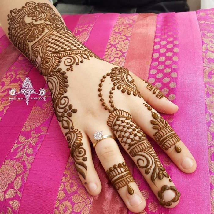 dessin détaillé au henné marron sur le poignet et doigts style dentelle