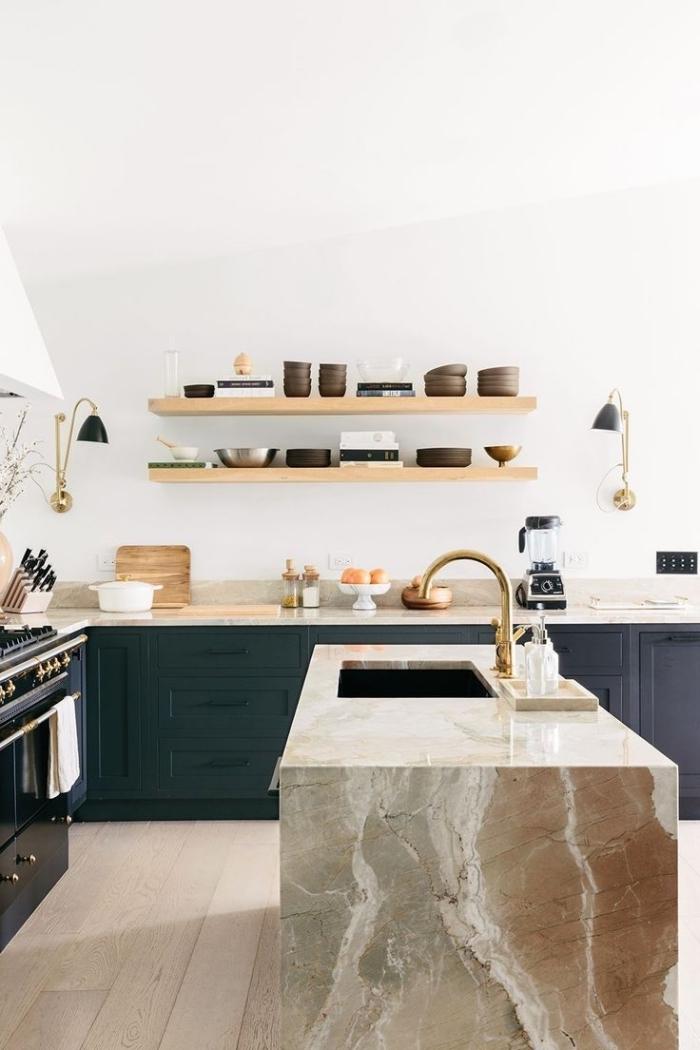 cuisine bleu canard de style rustique moderne avec des étagères ouvertes en bois et un ilot de cuisine contrastant en marbre avec évier doré
