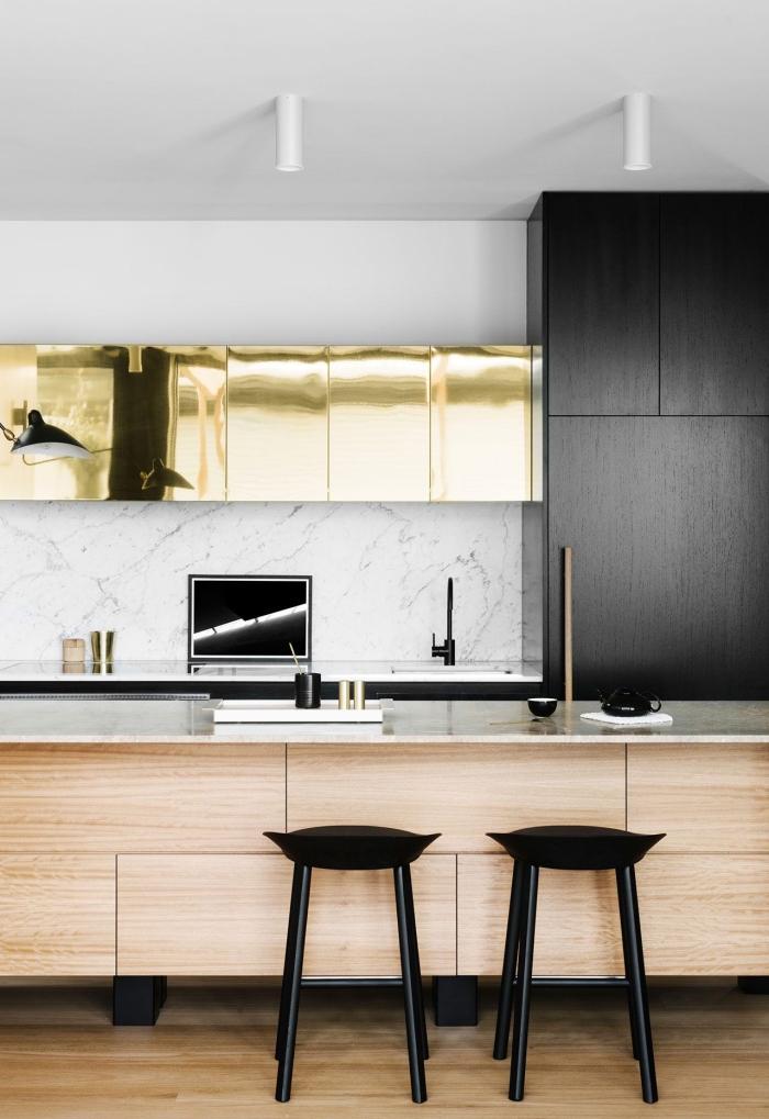 des effets de matières dans cette cuisine ilot central avec espace bar pour un look contemporain plein de caractères, des armoires de cuisine noir mat, or et bois