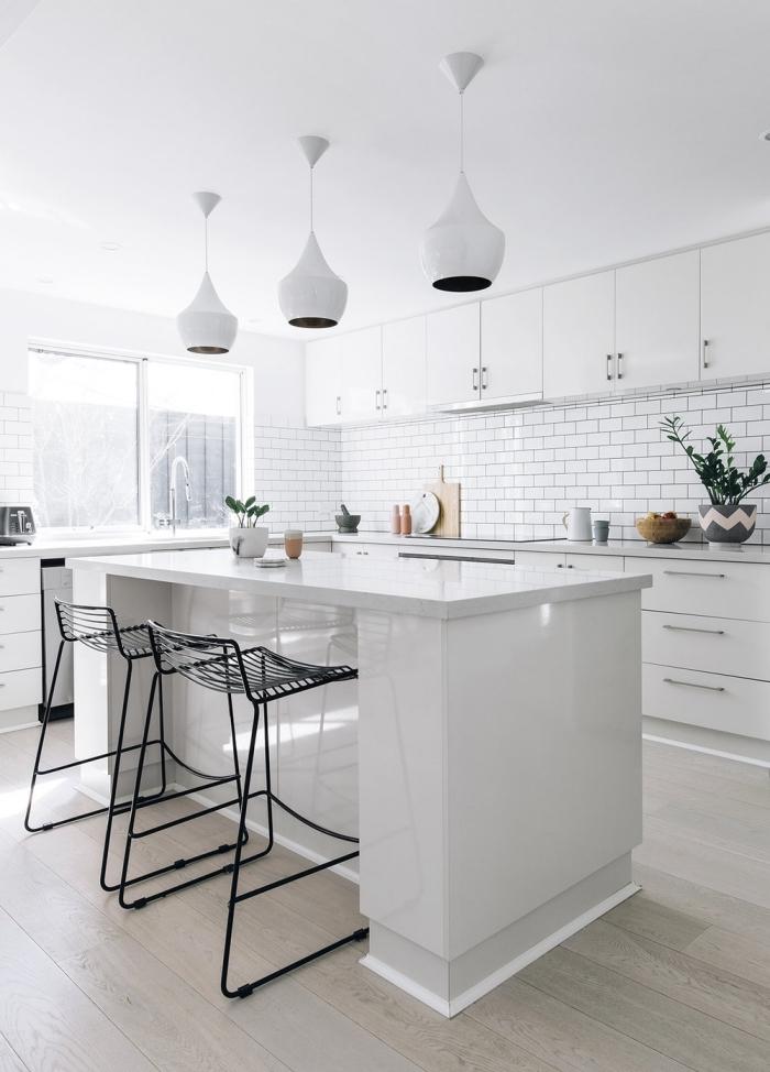 cuisine monochrome à finition laquée blanche avec crédence en carreaux de métro équipée d'un ilot central cuisine plan bar minimaliste
