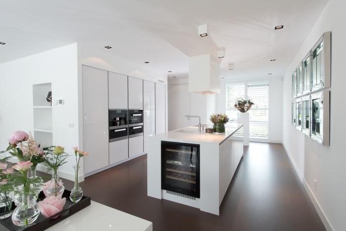cuisine blanche à finition laquée pleine de luminosité avec ilot centrale de lavage de même style avec un bar à vins intégré