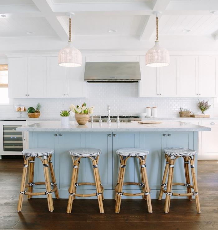 cuisine avec ilot blanc et bleu pastel de style bord de mer pleine de luminosité aux accents en bois et rotin