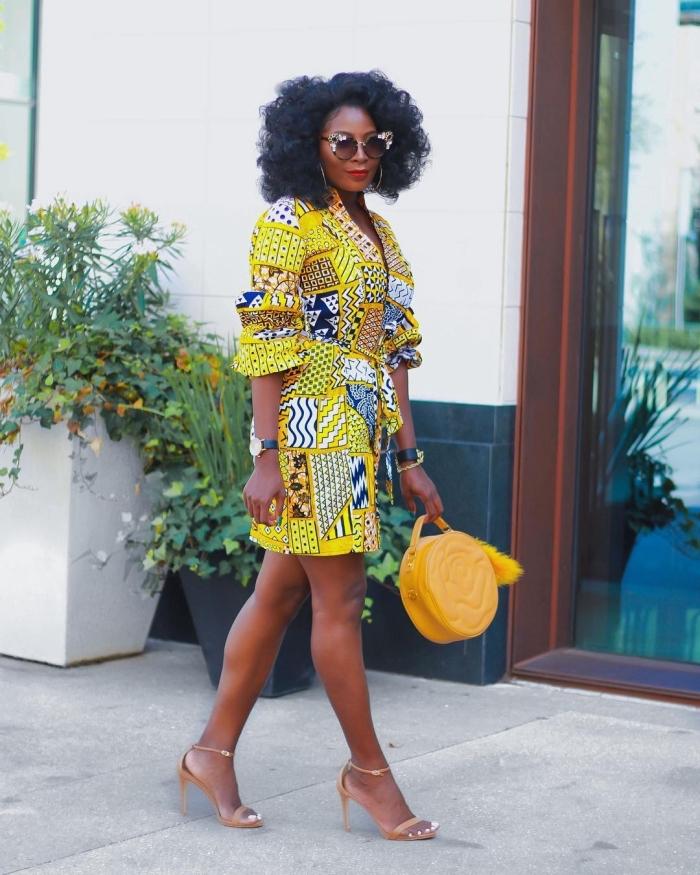 une robe coupe portefeuille à motif patchwork jaune assortie avec un petit sac rond et des sandales à talons chic, tenue wax élégante et chic