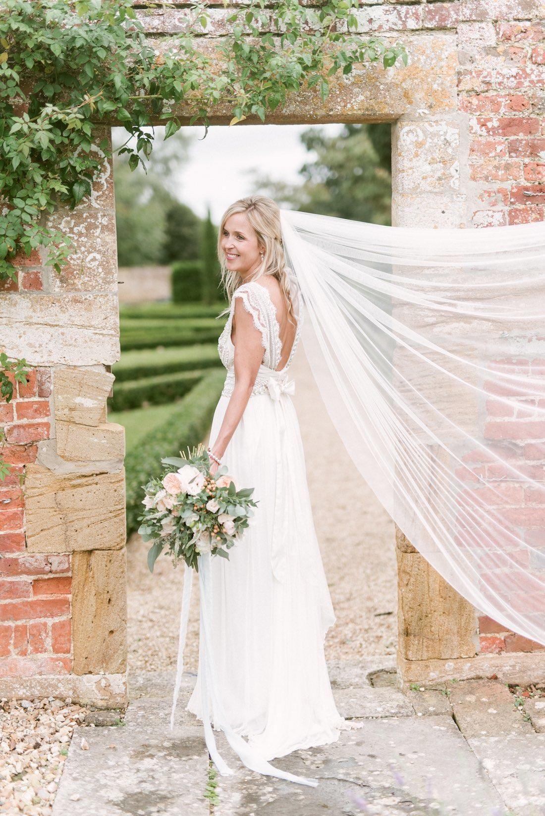 une robe de mariée bohème chic à dos nu en dentelle mis en valeur par un joli noeud à la taille et un voile léger