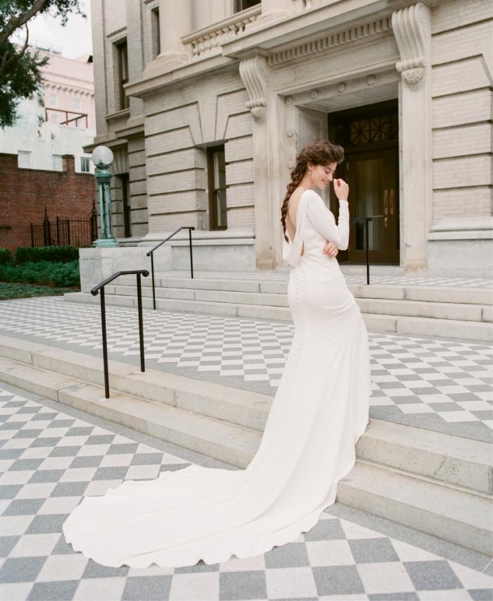 modèle de robe mariee dos nu au design unique avec une longue traîne majestueuse et un décolleté dos plongeant qui offre un vue spectaculaire de derrière