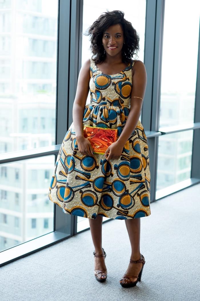 modele wax versatile pour un look casual ou professionnel, robe évasée à coupe féminine et à motifs africains en bleu et ocre, assortie avec une pochette métallisée