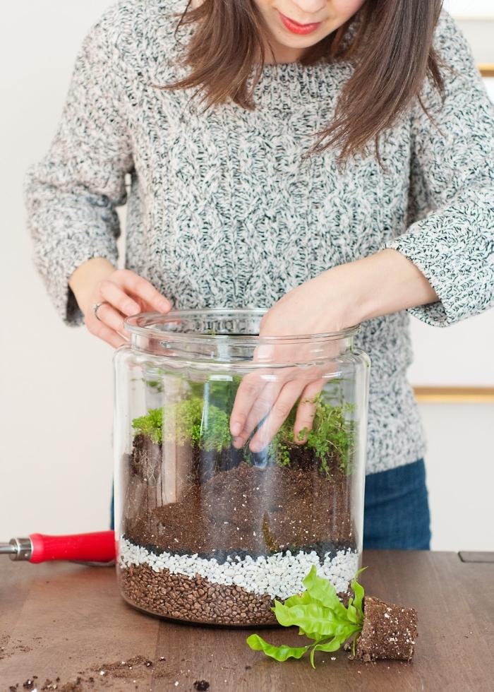 exemple comment remplir un gros bocal en alternant des couches de galets avec terreau pour plantes vertes